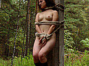 A busty girl in black boots is tied up in the woods