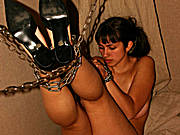 A girl wearing black dress in chains pisses on the floor standing